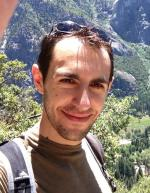 picture of Dan Frank, he is wearing sunglasses on his head and a backpack with landscape in background